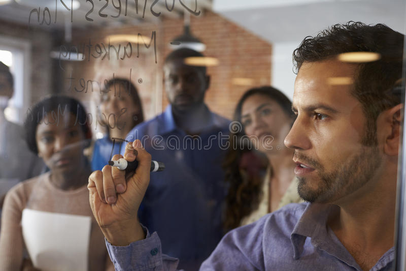 AffärsmanWriting Ideas On Glass skärm under möte arkivbild