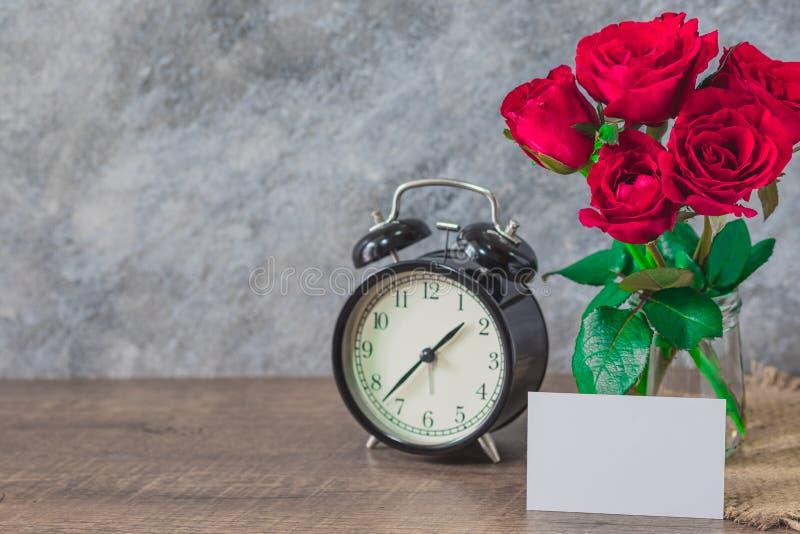 Affärsnamnkort med det vita mellanrumet på säcken och trätabellen med den röda härliga rosen, klockasvart cementbakgrund, royaltyfria foton