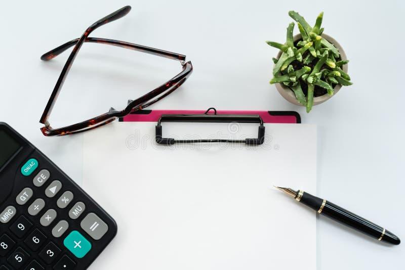 Affärsobjekt, skrivplatta med det tomma arket av papper, penna, exponeringsglas och räknemaskin på vit bakgrund fotografering för bildbyråer
