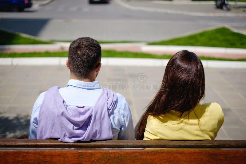 Affärspar bakifrån som sitter på bänken royaltyfri bild