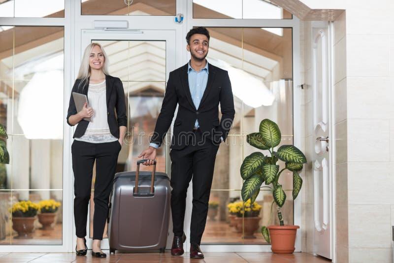 Affärspar i hotelllobby, Businesspeoplegruppman och kvinnagäster ankommer royaltyfria foton