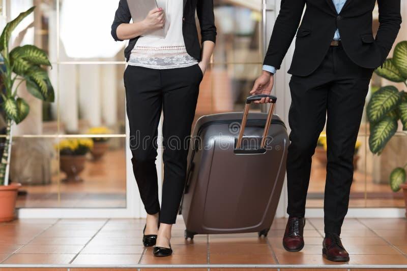 Affärspar i hotelllobby, Businesspeoplegruppman och kvinnagäster ankommer royaltyfri bild