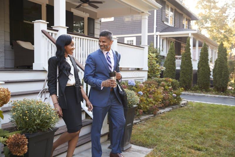 Affärspar som lämnar det förorts- huset för att pendlingssträcka ska arbeta royaltyfri bild