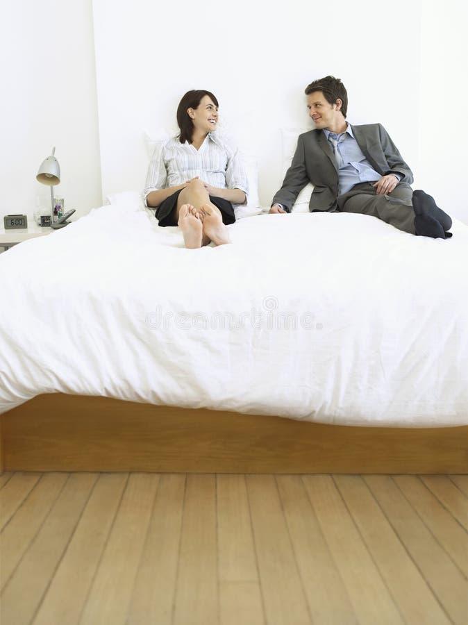 Affärspar som ler på säng arkivfoto