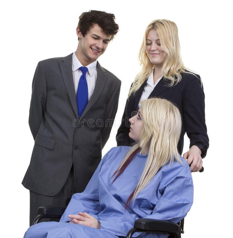 Affärspar som ser kvinnor som sitter på rullstolen arkivbild