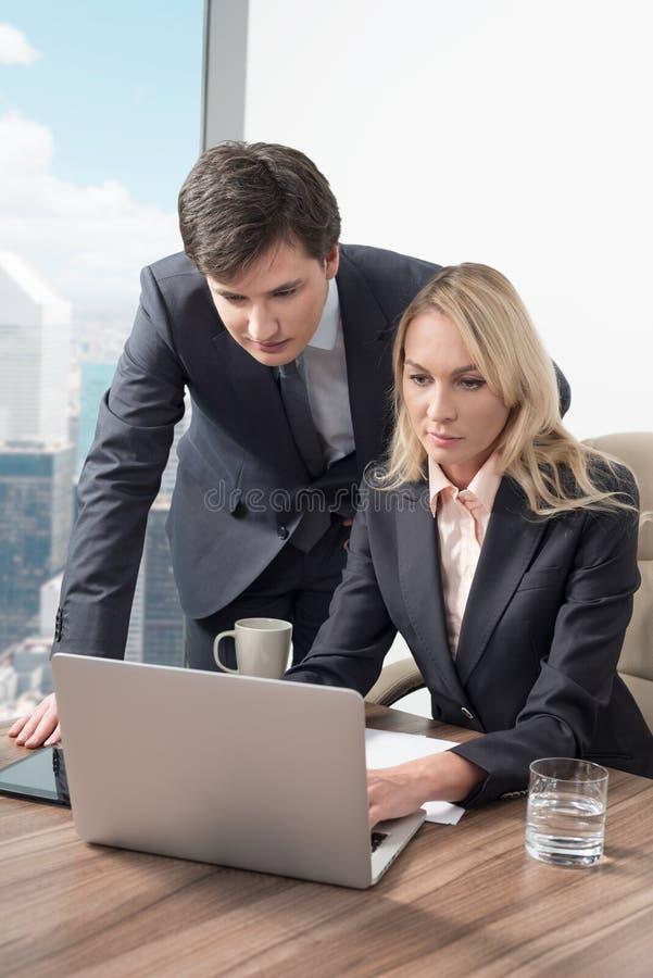 Affärsparet upptäcker någon nödvändig information om affär i bärbara datorn royaltyfri foto