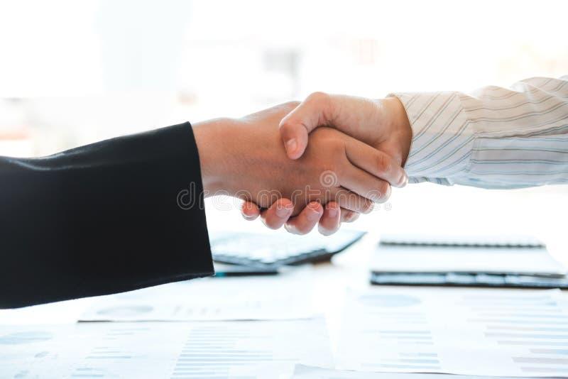 Affärspartnerkollegor som skakar händer som möter den nya finans för startprojektplan och ekonomigrafen med den lyckade bärbara d arkivfoto