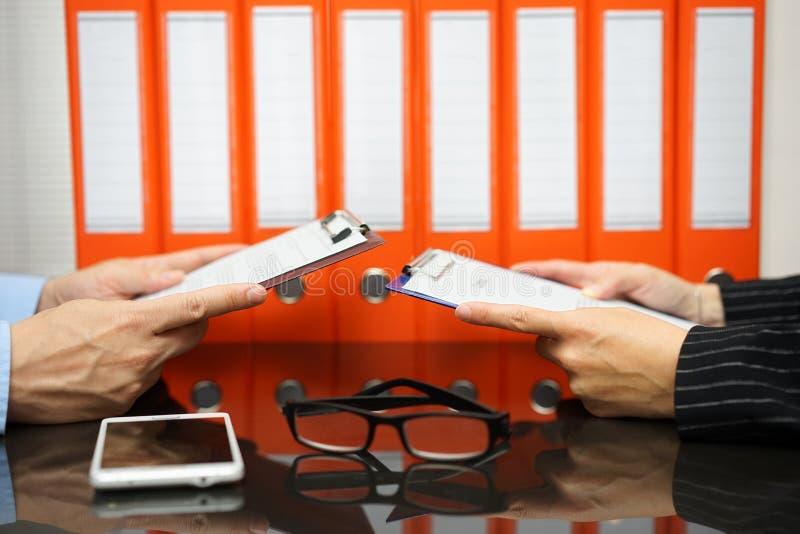 Affärspartners läser avtalet med dokumentation i bac arkivfoto