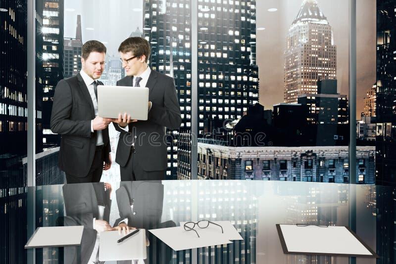 Affärspartners med bärbara datorn i regeringsställning med stor fönster och nig royaltyfria bilder