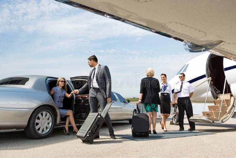 Affärspartners omkring som stiger ombord den privata strålen royaltyfri foto