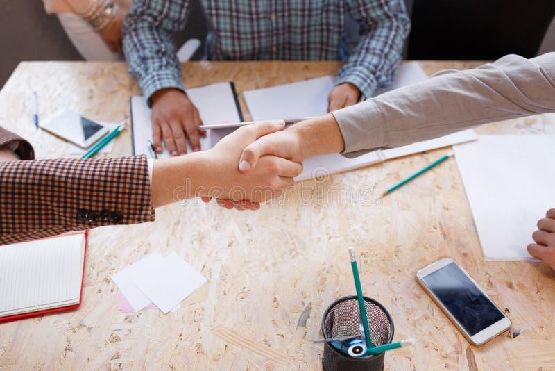 Affärspartners skakar händer i konferensrummet royaltyfri bild