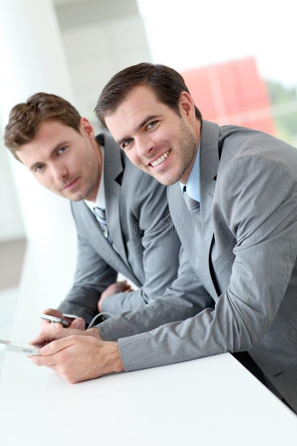 Affärspartners som använder smartphones i hall royaltyfri bild