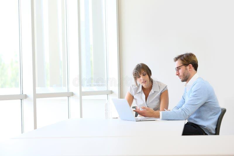 Affärspartners som arbetar på bärbara datorn royaltyfria bilder