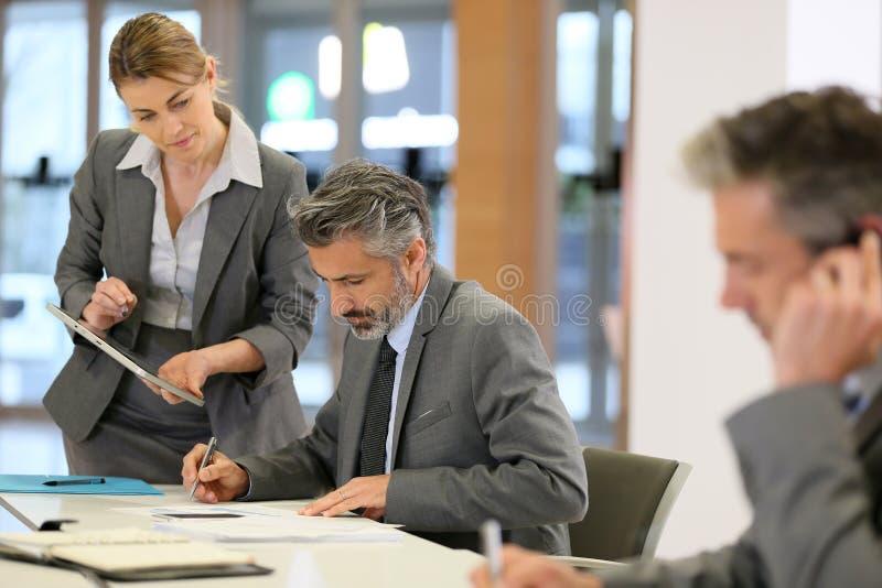 Affärspartners som diskuterar budgeten arkivfoto
