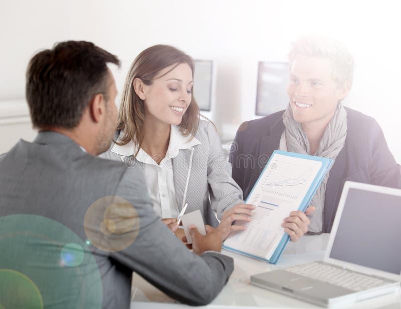 Affärspartners som diskuterar investeringar arkivbild