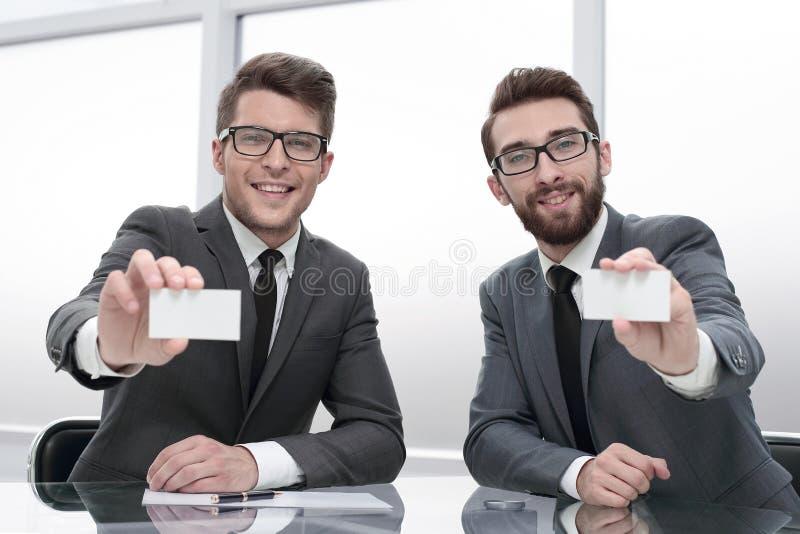 Affärspartners som erbjuder dig deras affärskort royaltyfri foto