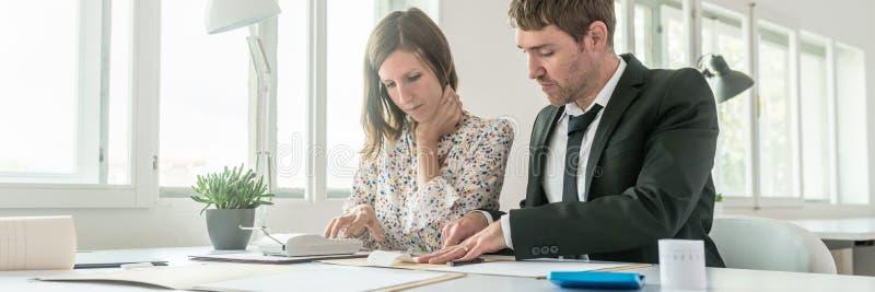 Affärspartners som gör beräkningar på en tillfoga maskin eller cal royaltyfri bild