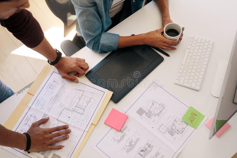 Affärspartners som i regeringsställning arbetar på arkitekturplan royaltyfri foto