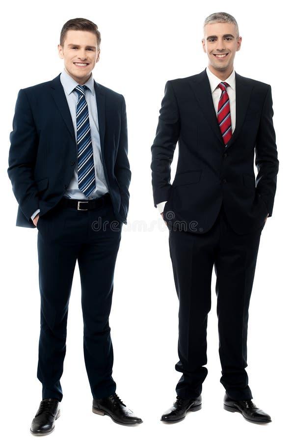 Affärspartners som poserar över vit royaltyfri bild