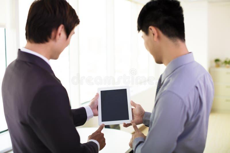 Affärspartners som ser minnestavlan royaltyfria bilder