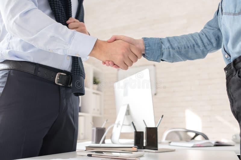 Affärspartners som skakar händer över tabellen arkivbilder