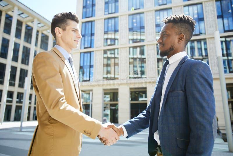 Affärspartners som skakar händer i finansiellt område royaltyfria foton