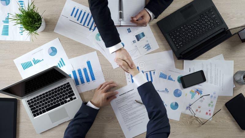 Affärspartners som skakar händer, undertecknande affärsavtal efter förhandlingar arkivbild
