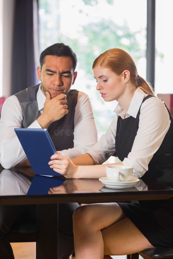 Affärspartners som tillsammans arbetar på minnestavlaPC i ett kafé royaltyfri foto