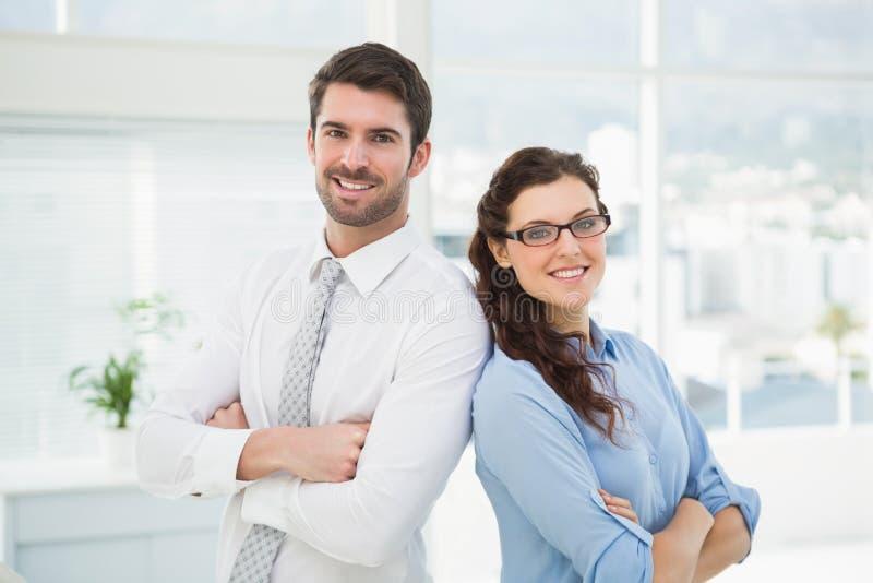 Affärspartners som tillsammans ler och poserar royaltyfri fotografi