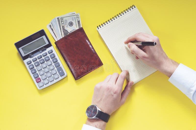 Affärspengar- och räknemaskinbegrepp på gul bakgrund arkivfoto