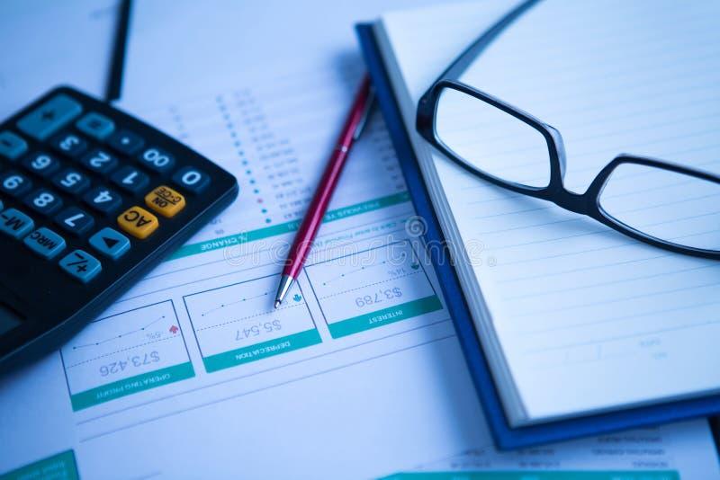 Affärspenna, räknemaskin och exponeringsglas på finansiellt diagram royaltyfria bilder