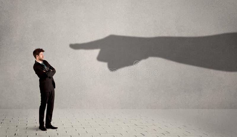 Affärsperson som ser den enorma skuggahanden som pekar på honom som är conc royaltyfri bild