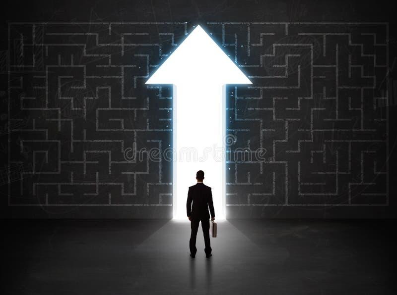 Affärsperson som ser labyrint med lösningspilen på väggen royaltyfri fotografi