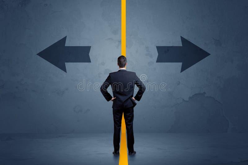 Affärspersonen som väljer mellan två alternativ, avskilde vid en skrän royaltyfri foto