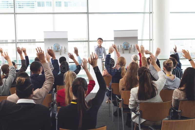 Affärsprofessionell som lyfter händer i ett affärsseminarium royaltyfri foto