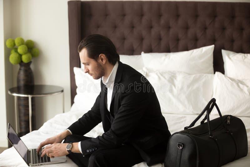 Affärsresande som arbetar på bärbara datorn i hotellrum arkivfoto