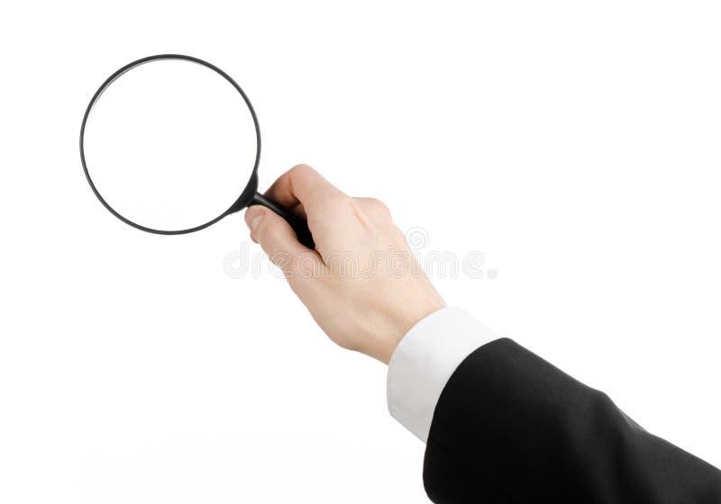 Affärssökandeämne: affärsmannen i en svart dräkt som rymmer ett förstoringsglas på en vit, isolerade bakgrund arkivfoton