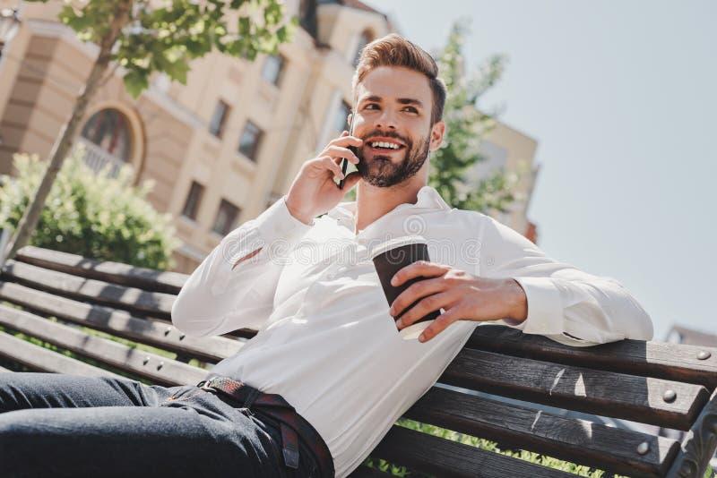 Affärssamtal Den unga mannen som sitter i, parkerar, talar på telefonen och dricker kaffe arkivfoto