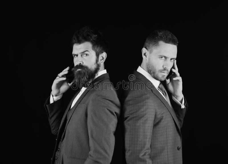 Affärssamtal och rivalitetbegrepp Affärsmän med säkra framsidor royaltyfria foton