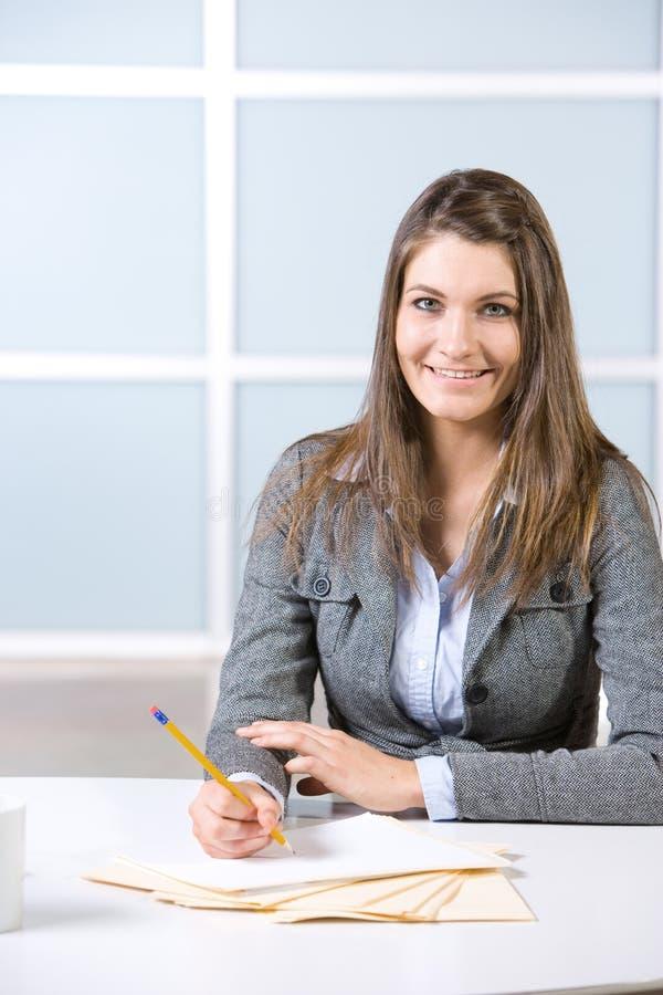 affärsskrivbordet bemärker kvinnawriting royaltyfri bild