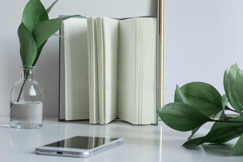 Affärsskrivbordet med anteckningsboken söker vastelefonen arkivfoto