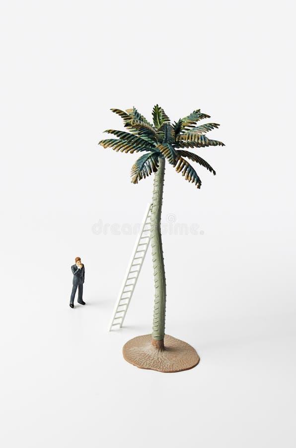 Affärsstatyett, stege och palmträd arkivbild
