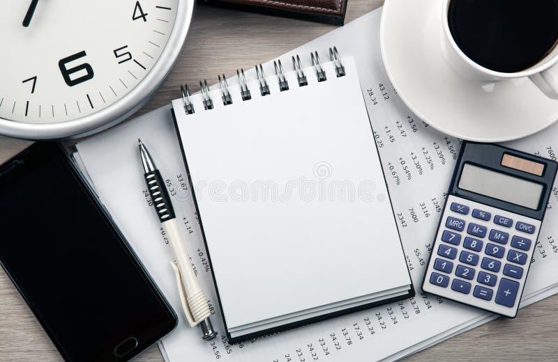 Affärsstilleben från en notepad, en smartphone, en klocka, en kopp kaffe, en räknemaskin fotografering för bildbyråer