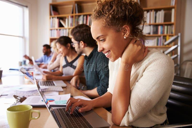 AffärsTeam Having Meeting In Busy kontor arkivbild