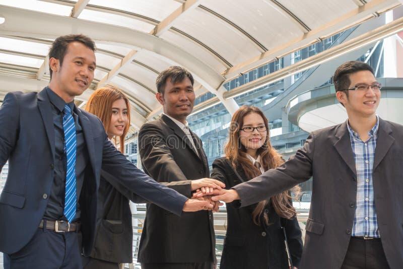 Affärsteamwork för fem asiat med en grupp människor med händer t arkivfoto