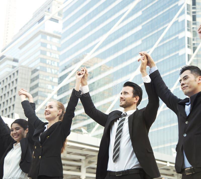 Affärsteamwork räcker upp begreppsberömframgång för arbete royaltyfri bild