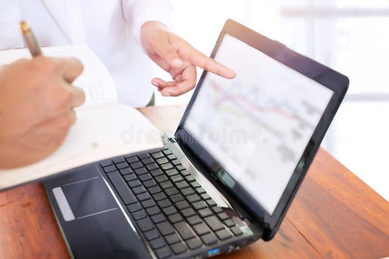 affärsteamwork som diskuterar data med en finansgraf på bärbar datordatoren på ett skrivbord royaltyfri fotografi