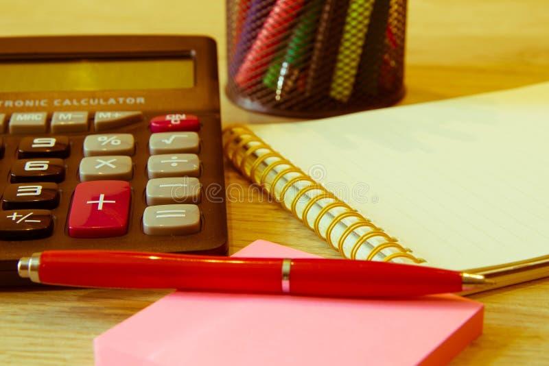 Affärstillbehören anteckningsbok, räknemaskinen, reservoarpennan och diagram, tabeller, kartlägger på ett träkontorsskrivbord royaltyfria foton