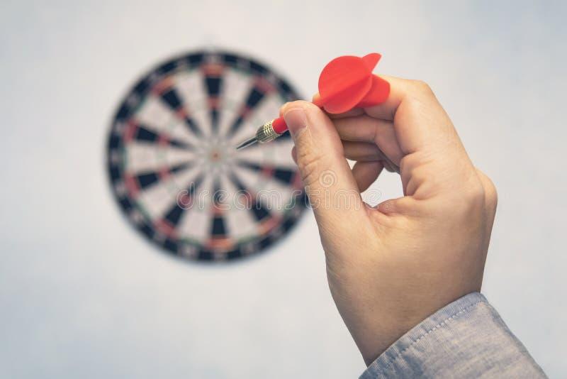Affärsutbildningsframgång och målbegrepp Tätt upp uppsätta som mål en hand den gröna pilpilen in mot mitten av darttavlan arkivfoton