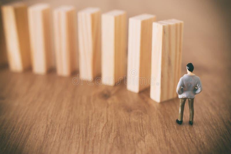 Aff?r En man står framme av dominobrickor och ordnar dem men är omedveten av faran av deras nedgång riskkontroll och arkivfoton